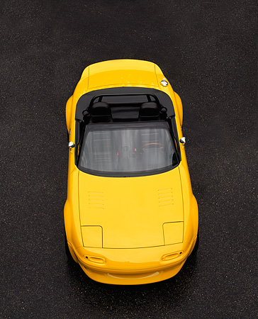 AUT 25 RK0093 05 © Kimball Stock 1997 Mazda Miata V8 Yellow Overhead Head On View On Pavement