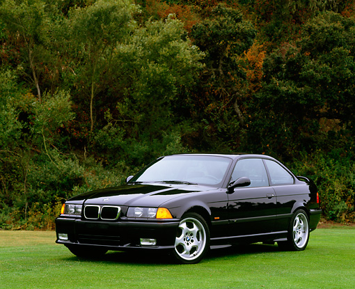 AUT 25 RK0147 03 © Kimball Stock 1997 BMW M3 Black 3/4 Front Parking Lights On By Trees On Grass