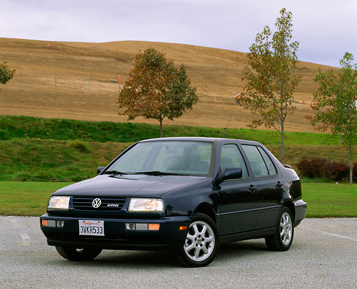 AUT 25 RK0185 04 © Kimball Stock 1997 Volkswagen Jetta GLX Black 3/4 Front View On Pavmement By Grass Hills