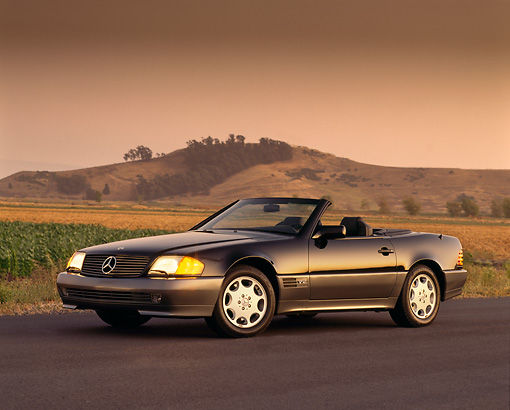 AUT 25 RK0192 11 © Kimball Stock 1994 Mercedes-Benz 600SL Roadster Black 3/4 Side On Road Headlights On By Dry Grass Mountains In Backgrnd