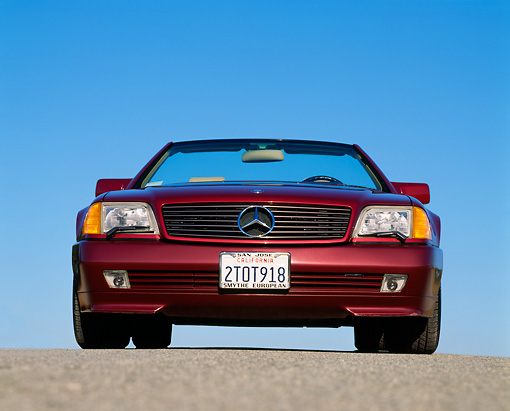 AUT 25 RK0222 01 © Kimball Stock 1991 Mercedes-Benz 500SL Convertible Burgundy Low Head On Shot On Pavement Blue Sky