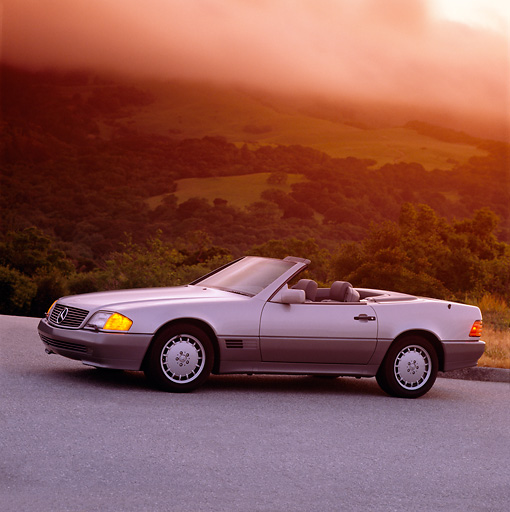 AUT 25 RK0237 01 © Kimball Stock 1990 Mercedes-Benz 500SL Convertible Silver 3/4 Side View On Pavement Filtered
