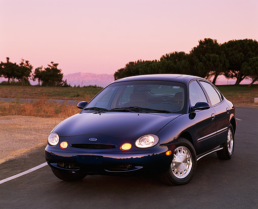 AUT 25 RK0302 10 © Kimball Stock 1996 Ford Taurus Blue 3/4 Front View On Pavement Trees Background At Dusk