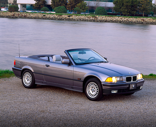 AUT 25 RK0389 06 © Kimball Stock 1995 BMW 318i Convertible Silver 3/4 Front View On Pavememnt By Water At Dusk