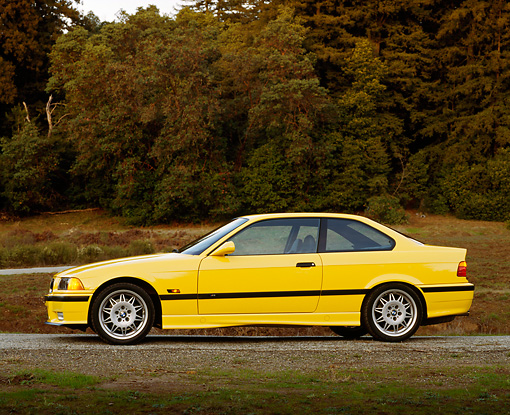 AUT 25 RK0414 03 © Kimball Stock 1995 BMW M3 Yellow Profile View On Gravel By Trees