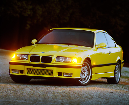 AUT 25 RK0422 01 © Kimball Stock 1995 BMW M3 Yellow 3/4 Front View On Pavement At Dusk