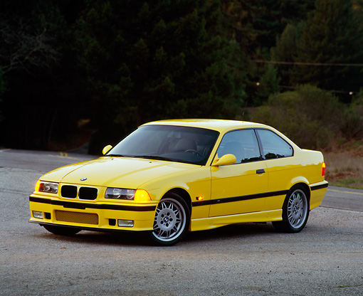 AUT 25 RK0424 02 © Kimball Stock 1995 BMW M3 Yellow 3/4 Front View On Pavement At Dusk