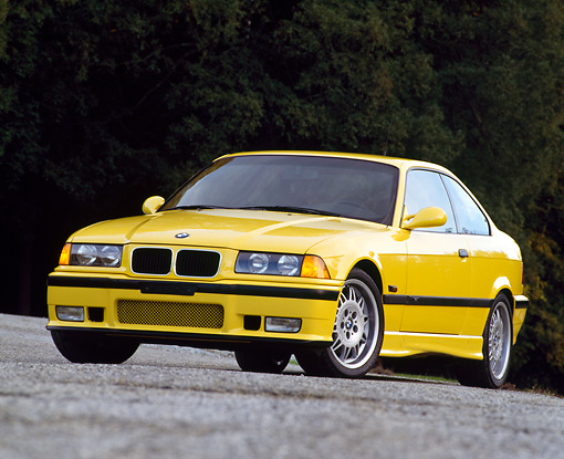AUT 25 RK0428 02 © Kimball Stock 1995 BMW M-3 Yellow Low 3/4 Front View On Pavement Dark Background