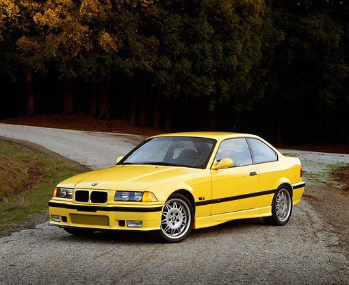 AUT 25 RK0429 02 © Kimball Stock 1995 BMW M3 Yellow 3/4 Front View On Pavement By Trees At Dusk