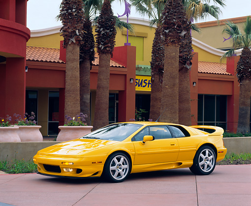 AUT 25 RK0433 07 © Kimball Stock 1997 Lotus Esprit V8 Yellow Side 3/4 View By Palm Trees And Buildings