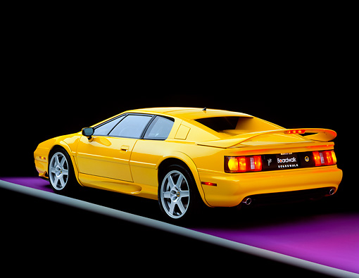AUT 25 RK0437 06 © Kimball Stock 1997 Lotus Esprit V8 Yellow Rear 3/4 View On Purple Floor Gray Line Studio