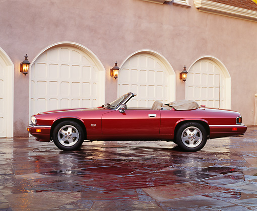 AUT 25 RK0459 08 © Kimball Stock 1995 Red XJS Jaguar Convertible Side View On Driveway In Front Of Garage Headlights On