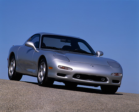 AUT 25 RK0474 08 © Kimball Stock 1992 Mazda RX7 Silver 3/4 Low Front Slanted View On Pavement Hill Blue Sky