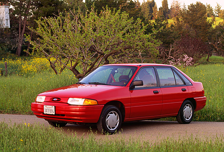 AUT 25 RK0487 01 © Kimball Stock 1993 Ford Escort Red 3/4 Front View By Tall Grass And Trees
