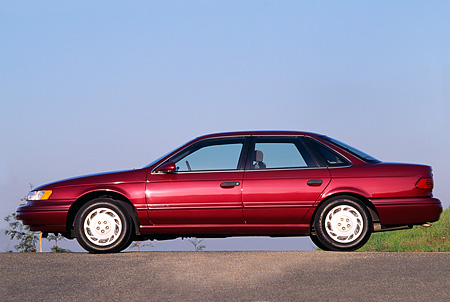 AUT 25 RK0493 02 © Kimball Stock 1993 Ford Taurus Burgundy Profile View On Pavement Blue Sky