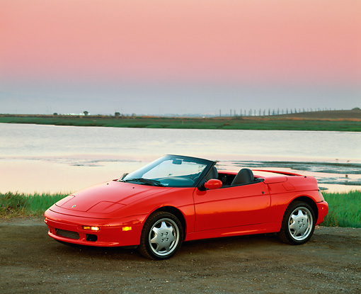 AUT 25 RK0512 02 © Kimball Stock 1991 Lotus Elan Convertible Red 3/4 Side View On Dirt By Water Filtered