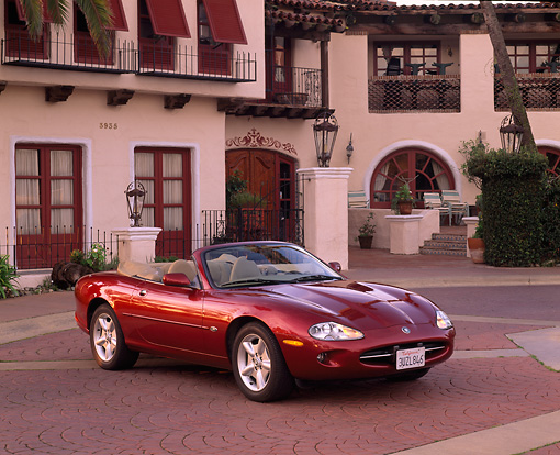 AUT 25 RK0542 06 © Kimball Stock 1997 Jaguar XK8 Convertible Red 3/4 Front View By Spanish Building