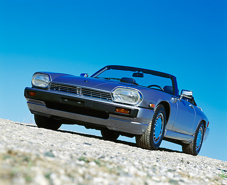 AUT 25 RK0589 02 © Kimball Stock 1990 Jaguar XJS Sport Convertible Blue 3/4 Low Front View On Pavement Blue Sky