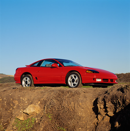 AUT 25 RK0602 01 © Kimball Stock 1991 Dodge Stealth Red 3/4 Low Side View By Dirt Cliff Blue Sky