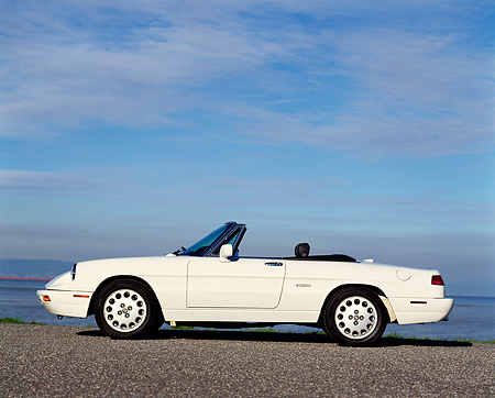 AUT 25 RK0624 04 © Kimball Stock 1994 Alfa Romeo Spider Veloce Convertible White Low Profile On Pavement Blue Sky