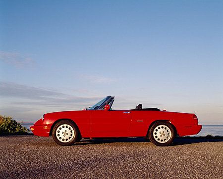 AUT 25 RK0631 05 © Kimball Stock 1994 Alfa Romeo Spider Veloce Convertible Red Profile On Pavement Blue Sky