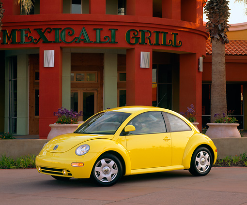AUT 25 RK0682 09 © Kimball Stock 1998 Volkswagen Beetle, Yellow slight 3/4 on pavement, lights on in front of red building with palm trees and flower planters