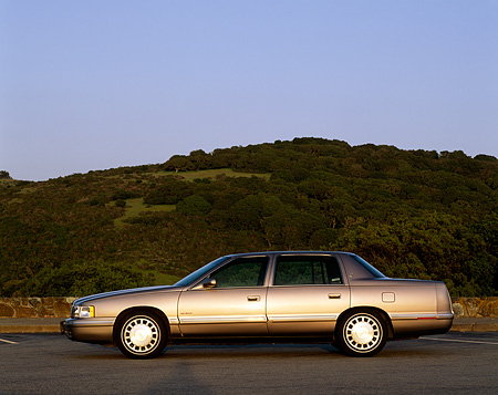 AUT 25 RK0707 02 © Kimball Stock 1998 Cadillac De Ville Champagne Profile On Pavement Hills Blue Sky