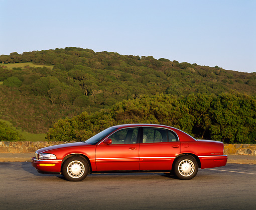 AUT 25 RK0713 04 © Kimball Stock 1999 Buick Park Avenue Red Side View On Pavement Hills Blue Sky