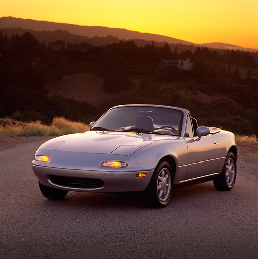 AUT 25 RK0767 03 © Kimball Stock 1990 Mazda Miata Convertible Silver 3/4 Front View On Pavement Hills Background At Dusk