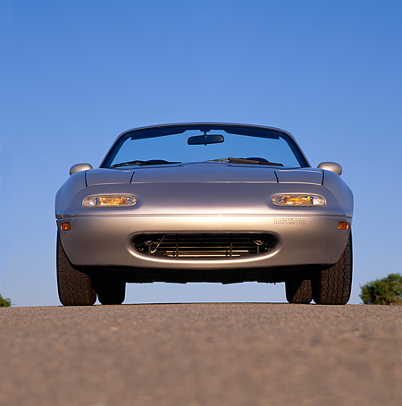 AUT 25 RK0769 05 © Kimball Stock 1990 Mazda Miata Convertible Silver Low Head On Shot On Pavement Blue Sky
