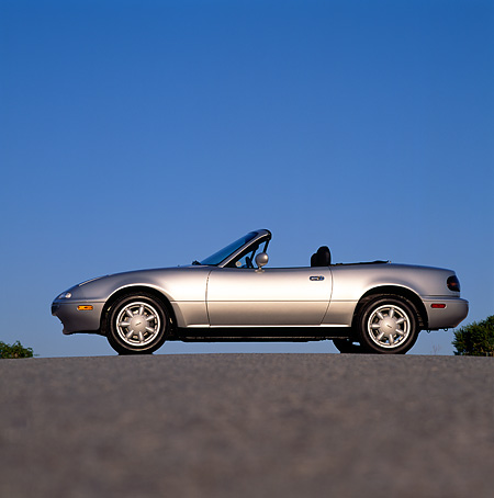 AUT 25 RK0772 03 © Kimball Stock 1990 Mazda Miata Convertible Silver Low Profile View On Pavement Blue Sky