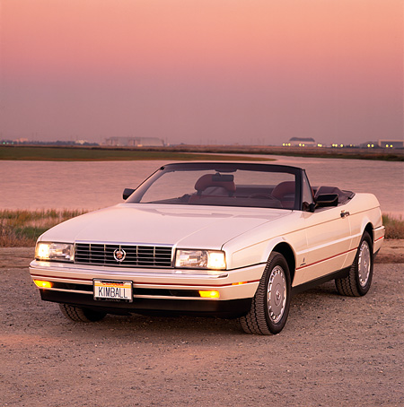 AUT 25 RK0785 05 © Kimball Stock 1990 Cadillac Allante Silver Front 3/4 View On Gravel By Water At Dusk