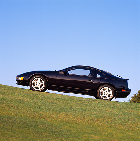 AUT 25 RK0790 02 © Kimball Stock 1990 Nissan 300ZX Turbo Black Slanted Side View On Grass Blue Sky