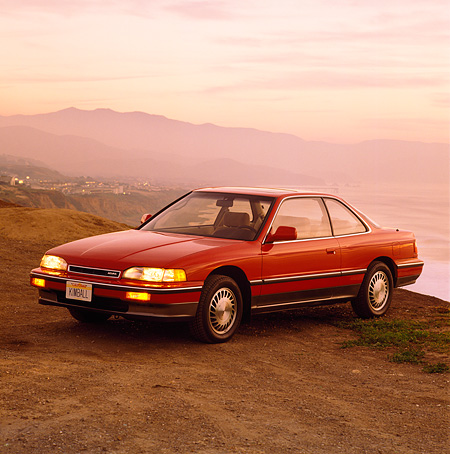 AUT 25 RK0809 04 © Kimball Stock 1990 Acura Legend Red 3/4 Front View On Dirt Mountains Background