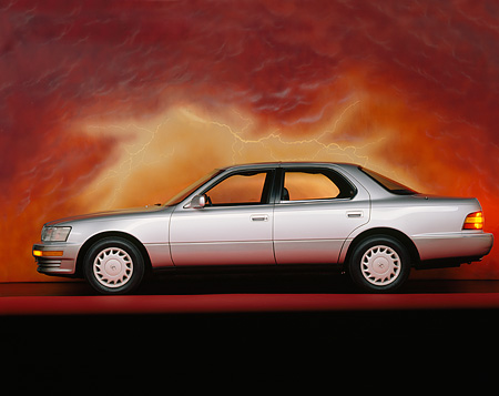 AUT 25 RK0828 03 © Kimball Stock 1990 Lexus Silver Profile View On Red Line Orange Clouds Background Studio