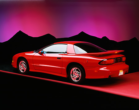 AUT 25 RK0840 04 © Kimball Stock 1993 Pontiac Trans Am Red  Rear 3/4 On Red Floor Purple Mountains Background