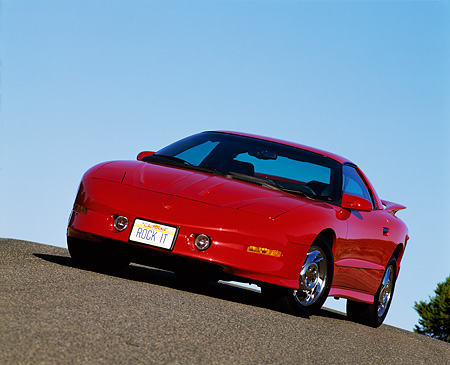 AUT 25 RK0852 12 © Kimball Stock 1993 Pontiac Firebird Trans Am Red Slanted 3/4 Front View On Pavement Hill Blue Sky