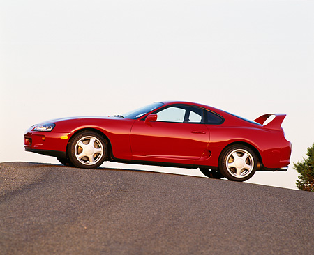 AUT 25 RK0863 01 © Kimball Stock 1993 Toyota Supra Red 3/4 Front View On Pavement Hill Blue Sky