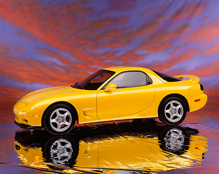 AUT 25 RK0895 02 © Kimball Stock 1993 Mazda RX7 R1 Yellow Side 3/4 View On Mylar Floor Sunset Sky