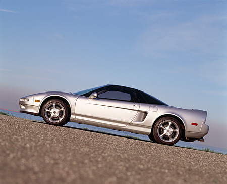 AUT 25 RK0920 05 © Kimball Stock 1993 Acura NSX Silver Slanted Profile View On Pavement Hill Blue Sky