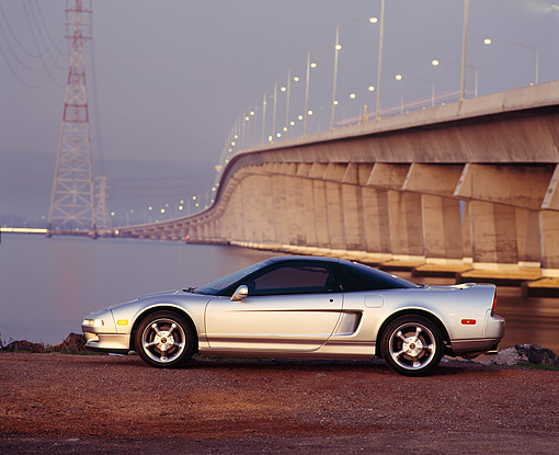 AUT 25 RK0927 06 © Kimball Stock 1993 Acura NSX Silver Profile View On Dirt By Bridge And Water At Night