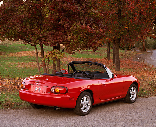 AUT 25 RK0985 05 © Kimball Stock 1999 Mazda Miata MX5 Convertible Red 3/4 Rear View On Pavement By Trees