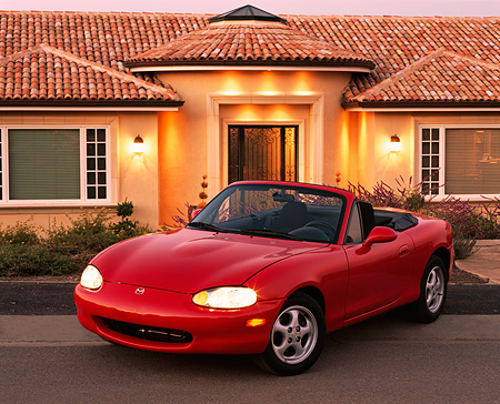 AUT 25 RK0990 04 © Kimball Stock 1999 Mazda Miata MX5 Convertible Red 3/4 Front View On Pavement By House