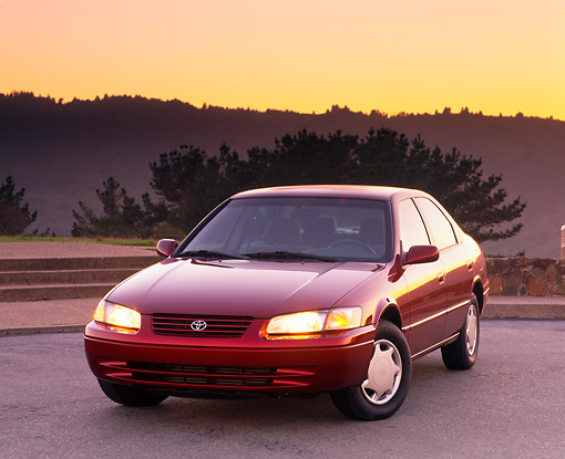 AUT 25 RK1014 07 © Kimball Stock 1999 Toyota Camry CE Vintage REd 3/4 Front View On Pavement At Dusk