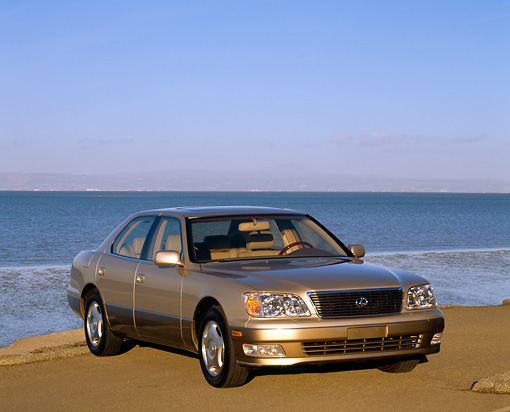 AUT 25 RK1029 04 © Kimball Stock 1999 Lexus LS400 Gold 3/4 Front View On Sand By Water Blue Sky