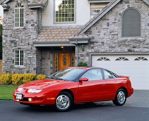AUT 25 RK1032 06 © Kimball Stock 1999 Saturn 3 Door Coupe Red 3/4 Side View On Driveway By House