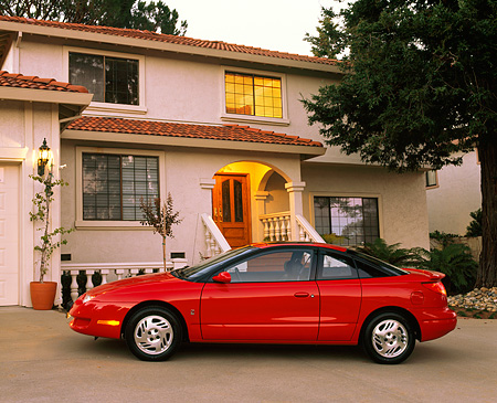 AUT 25 RK1034 03 © Kimball Stock 1999 Saturn SC 3 Door Coupe Red Profile View On Driveway By House At Dusk
