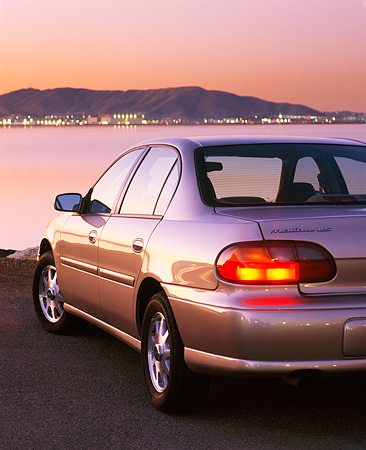AUT 25 RK1048 01 © Kimball Stock 1999 Chevrolet Malibu Champagne 3/4 Rear View On Sand By Water At Night