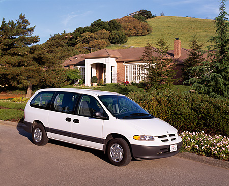 AUT 25 RK1060 01 © Kimball Stock 1996 Dodge Caravan White Front 3/4 View On Pavement By Trees And Bushes