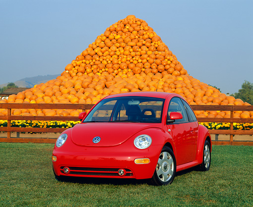AUT 25 RK1093 06 © Kimball Stock 1999 Volkswagen Beetle Turbo Red 3/4 Front View On Grass Pumpkins Background